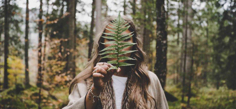 Mujer en el bosque cubriéndose con una hoja. Representa infraestructura verde